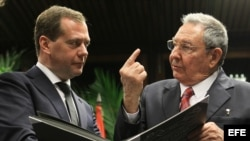 El primer ministro de Rusia Dimitri Medvedev (iz) y Raúl Castro observando un album de fotos.