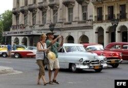 Una pareja de turistas camina por una calle de La Habana.