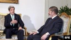 El presidente de Egipto, Mohamed Mursi (dcha) conversa con el secretario de Estado de Estados Unidos, John Kerry (izq).