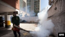 Un empleado de la Alcaldía de Chacao, en Caracas, fumiga un estacionamiento como medida preventiva contra el Zika.