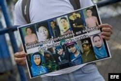 Un joven sostiene un cartel con fotografías de manifestantes detenidos.