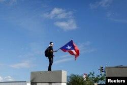 Un hombre ondea la bandera de Puerto Rico durante la protesta de este lunes contra Rosselló.