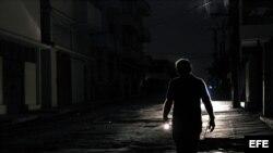 Un hombre camina con una linterna por el barrio de El Cerro, en La Habana, durante un apagón. EFE/Alejandro Ernesto