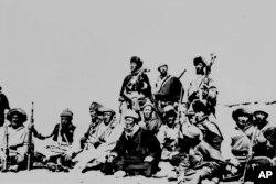Fotografía de archivo de marzo 1959 del Dalai Lama, sentado al centro, descansando con guerreros que lo protegieron en el Himalaya después de huir de la capital Lhasa.