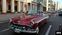 Turistas en un viejo auto descapotable, por el malecón de La Habana.