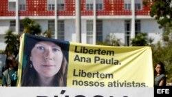Simpatizantes del grupo ecologista Greenpeace sostienen pancarta con una imagen de la activista brasileña Ana Paula durante una protesta frente a la embajada de Rusia en Brasil