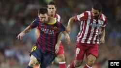 El delantero argentino del FC Barcelona, Leo Messi (i), lucha el balón junto al turco Arda Turan, del Atlético de Madrid