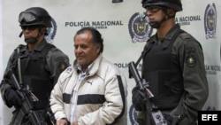 Archivo - Efectivos de la policía colombiana escoltan a Hely Mejía Mendoza (c), destacado cabecilla de las FARC conocido con el alias de 'Martín Sombra', quien fuera capturado en el departamento de Boyacá y presentado hoy, 26 de febrero de 2008, en Bogotá