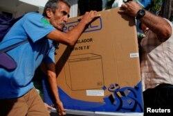 El chofer Héctor Castro carga un refrigerador comprado el lunes en una de las tiendas en La Habana (Foto: Alexandre Meneghini/Reuters).