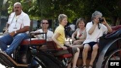 Un grupo de turistas pasea en coche por una calle de La Habana.