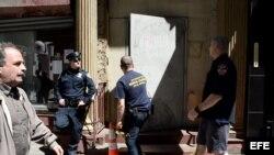 Un policía monta guardia mientras bomberos entran a un edificio en Park Place en el bajo Manhattan, donde una pieza de uno de los aviones destruidos en los ataques del 11 de septiembre fue descubierto en Nueva York (EE.UU.).