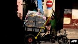 Un hombre transporta pan en un triciclo en una zona en cuarentena por COVID-19 en La Habana. (YAMIL LAGE / AFP)
