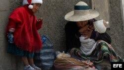 Una niña campesina junto a su madre piden limosna en las calles de La Paz (Bolivia).