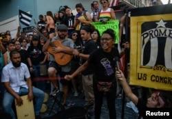 Miembros del grupo de teatro Papel Machete actúan durante la protesta de este lunes en San Juan.