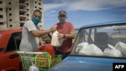 Dos hombres acomodan la mercancía adquirida en una de las tiendas en dólares abiertas la semana pasada en Cuba. (Adalberto Roque / AFP)