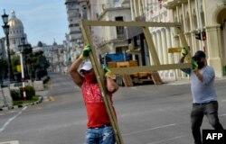 Trabajadores de un hotel próximo al Paseo del Prado cuando se preparaban para proteger el fin de semana las ventanas de la instalación (Yamil Lage/AFP).