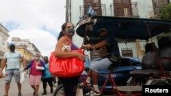 Una mujer con su gato en la bolsa en una calle de La Habana, en medio del peor rebrote de COVID-19 que ha vivido la capital. REUTERS/Stringer