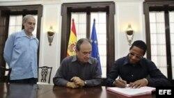 Javier Sotomayor firma hoy, viernes 25 de septiembre de 2015, la concesión de la nacionalidad española, en un acto encabezado por el cónsul general de España en Cuba, Jorge Montenegro y el embajador de España en la isla, Francisco Montalbán (d-i).