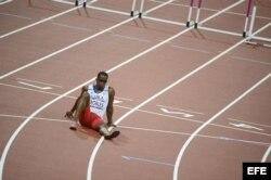 El cubano Dayron Robles se sienta en la pista en frustración por no terminar la prueba de los 110 metros vallas masculino.