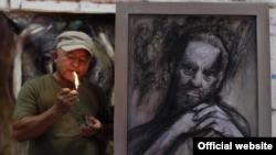 Nelson Domínguez fuma junto a una de sus obras inspiradas en Fidel Castro.