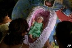 Peyton, de dos días de edad, yace en una canasta mientras su familia la cuida en su departamento