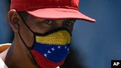 Un hombre viste una mascarilla con la bandera de Venezuela en una calle de Caracas. (AP/Matias Delacroix)