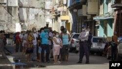 La policía controla la cola en una de las nuevas tiendas en dólares. (Adalberto ROQUE / AFP)