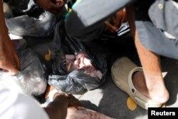 Jóvenes que buscan comida en un basurero en Caracas hallan trozos de carne cruda, el 27 de febrero de 2019.