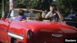 Un turista toma fotos desde un carro en La Habana.