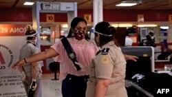 Pasajeros pasan controles por coronavirus tras la llegada al aeropuerto de La Habana.