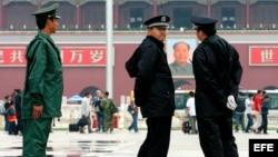 Archivo - Policias vigilan las entradas y salidas en la plaza de Tiananmen, en Pekín, China.