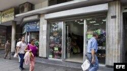 Varias personas caminan frente a un establecimiento comercial. Archivo