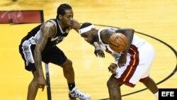 El jugador de los Spurs de San Antonio Kawhi Leonard (i) le aleja el balón a LeBron James (d), del Miami Heat, el martes 10 de junio de 2014.