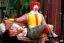Fotografía de archivo del 27 de mayo de 1998 de un hombre chino durmiendo en las piernas de un maniquí de Ronald McDonald afuera de un restaurante McDonald's en el sur de la plaza Tiananmen de Beijing. McDonald's abrió su primera sucursal en China en 1990.
