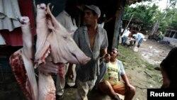 Agricultores descansan después de la matanza de un cerdo en una granja en las afueras de La Habana. (Archivo)