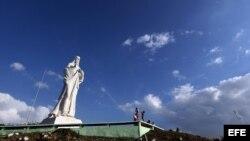 Turistas toman fotos del Cristo de La Habana en La Habana (Cuba). El cardenal cubano Jaime Ortega bendijo este gigantesco monumento, ubicado en una colina frente a la bahía desde la que se avista toda la ciudad, tras concluir las obras de restauración a l