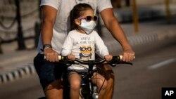 Una niña transportada en bicicleta usa un nasobuco para evitar el contagio del coronavirus, en La Habana, Cuba. AP Photo/Ramon Espinosa