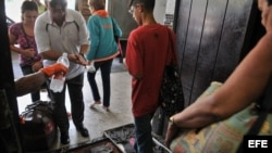Pasajeros pasan por un control sanitario en la terminal de ómnibus de La Habana tras registrarse un brote de cólera en la isla.