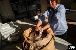 """Una empleada del gobierno alemán tras la caída del Muro de Berlín recupera documentos de bolsas marcadas """"para destruir"""" en lo que fuera la sede de la STASI (Foto: John MacDougall/AFP)."""