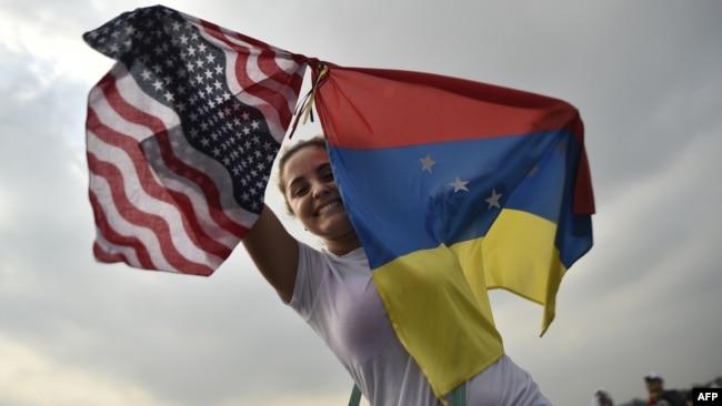 Una mujer sostiene las banderas de Venezuela y EEUU en el concierto de apoyo a la ayuda humanitaria en Cúcuta, en febrero pasado.