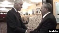 Bill Clinton y Raúl Castro se toman efusivamente de las manos.