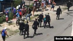 Foto Archivo. Boinas negras caminan junto a personas que permanecen en una cola.