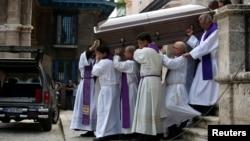 Miembros del clero cargan el ataúd con los restos del cardenal Jaime Ortega Alamino.
