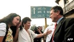 Magalys de Armas, esposa del opositor Vladimiro Roca, y su hija saludan a Michael Georges Kozak(R), en el Tribunal Municipal de Marianao. AFP/ADALBERTO ROQUE