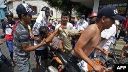Los manifestantes venezolanos cargan a un manifestante lesionado en una motocicleta durante una protesta en la ciudad fronteriza de Urena, Tachira, después de que el gobierno del presidente Nicolás Maduro ordenara un cierre temporal de la frontera con Col