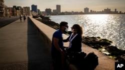 Una pareja de enamorados se proteje del coronavirus en el Malecón de La Habana.