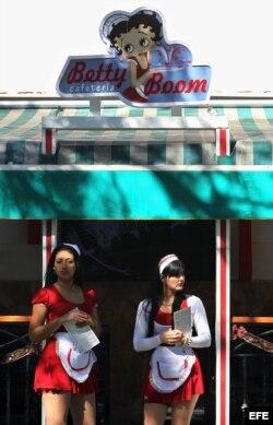 Dos meseras permanecen en la puerta de una cafetería en una calle de La Habana.