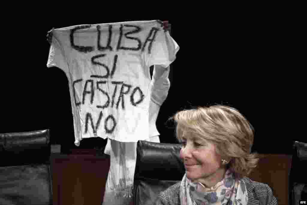 """La presidenta del PP de Madrid, Esperanza Aguirre (d), mientras una participante muestra una pancarta durante el acto organizado hoy en la Casa de América de Madrid bajo el título """"Damas de Blanco: Un mensaje de Cuba"""". En el acto se ha producido un enfren"""