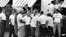 Un grupo de cubanos esperan entrar en una casa de Miami para alistarse y luchar contra Castro, el 18 de abril de 1961.