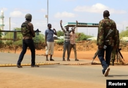 Oficiales de seguridad de Kenia interrogan a civiles en la carretera de Mandera donde fueron secuestrados los médicos cubanos.